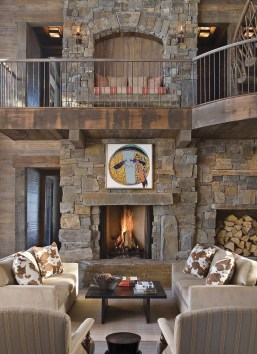 The interior walls, lined with hand scorped, oiled, and waxed Idaho pine, have a faint whitewashed effect, offset by the slightly darker grey tints in the surrounding rock chimneys and the cool slate floors, while strategically placed artwork adds splashe
