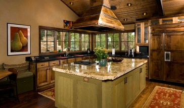 The kitchen is crowned by a hand-patinaed copper hood and ample windows overlook the patio yard and creek beyond.