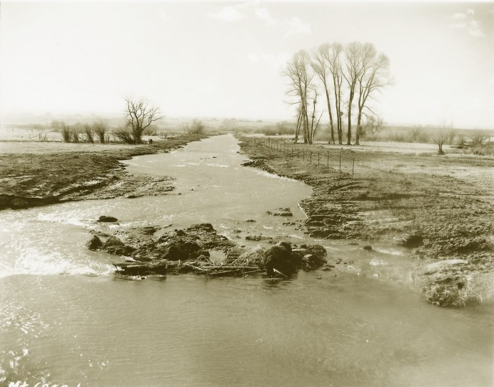 The information typewritten onto the back of this photograph reads: Lewistown, Mont. A part of Spring Creek, formerly a meandering creek, which has now been straightened, 4,200 feet of creek were shortened into 2,200 feet of straight chute, destroying