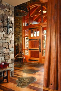 River rock stepping stones lead from the alder entry door custom made by Gary Ince Construction. The locksets, hinges, and hardware were custom built by Trapper Peak Forge.
