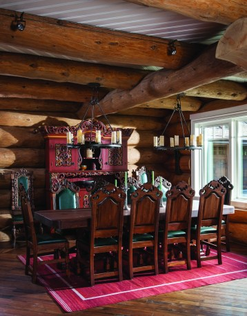In the dinning room, lowered ceilings provide a sense of warmth. The white framed windows hone in on the outdoor views. The furniture was hand-carved and imported from Norway.