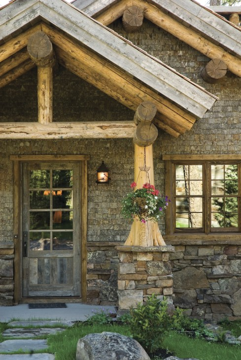Lichen covers the rock wainscoting and reclaimed cedar shake siding in the entryway, giving visitors the feeling that this new cabin has been around for decades.