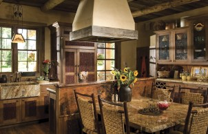 Custom willow front cabinetry adds color and texture to the cozy kitchen and dining area. The granite sink and counters and copper-backed cooking island provide an inorganic contrast to the rich palette of reclaimed wood surfaces.