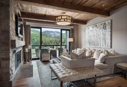 """Combining rustic elements in a contemporary setting helped transform the condo into a """"chalet,"""" as the Locatis refer to their getaway in the private Yellowstone Club village. A Carol Spielman painting hangs above the generously appointed, custom-made couch."""
