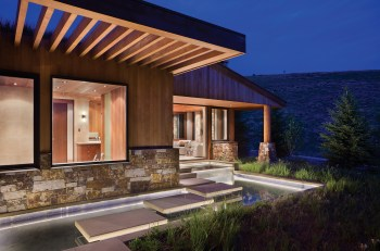 Stepping stones seem to float on a water feature that wraps around the exterior of the house, where the material palette of stone and wood are reflected in the water.