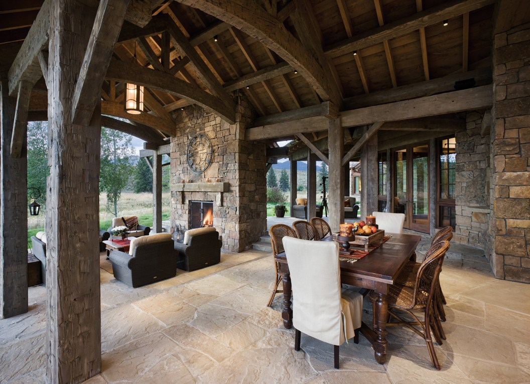 Celebrating the organic materials, stone and reclaimed lumber, the outdoor living areas are designed to be as comfortable as the interior furnishings. Slipcovers at the dining area and oversized chairs around the fireplace give the sense of indoor comfort.