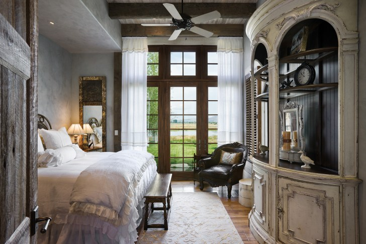 The guest bedroom opens to an ethereally sky-blue color on the wax-rubbed plaster walls. A curved Habersham hutch adds a lavish visual focal point to the room.