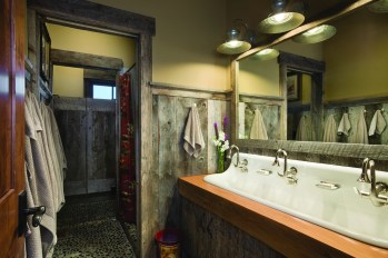 The luxury camping-themed bathroom with utility sink for three, features pebbled flooring and swinging doors.
