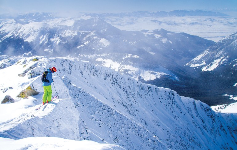 A skier stands near the top of the Lone Lake Cirque area just outside the resort boundary on the north side of Lone Peak. This zone is not patrolled and is considered backcountry terrain.   Photo by Ryan Day Thompson