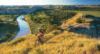 The Little Missouri River winds its way in the bottomland, while riders crest on a single-track above it. Photo by Chuck Haney
