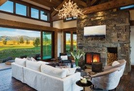 The dark, textured, fir flooring complements the stonework on the fireplace and the reclaimed timbers overhead.