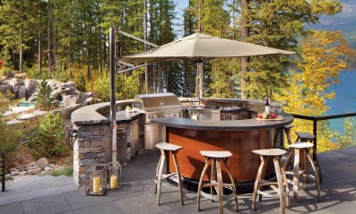 A large, 16-foot Tuuci umbrella shades a modern, curved bar and grilling station.