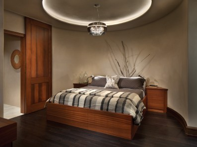 The team turned what used to be a wine room into a bedroom, complete with a custom bed and handblown glass chandelier.