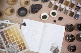 Test tiles and glaze samples lie beside Matt Fiske's material studies.