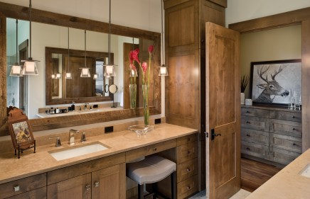 In each bathroom and indeed throughout the home, cabinets handcrafted by Wilson Cabinetry in Billings offer ample space for home organization and storage.
