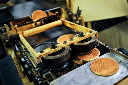 Stroopwafels fresh off the cookie trimmer, which makes them perfectly round before they're popped onto the conveyer belt to be sliced in half.