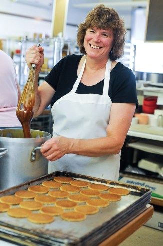Judy Boogman whisks a large pot of caramel before it is spread onto cookies.