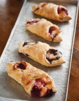 The front case is packed with delicious baked goods like these raspberry and blueberry cream cheese pastries.