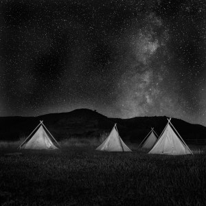 Sometime after midnight, on the Willow Creek Ranch, the Milky Way illuminates cowboy tepees at the camp where Butch Cassidy's cabin once stood.