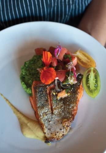Copper River salmon served with minted peas, heirloom tomato salad, miso-garbanzo puree, topped with a nasturtium.