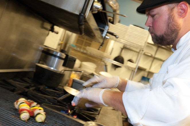 Sous chef Gabe Elam prepares grilled scallop kabobs.