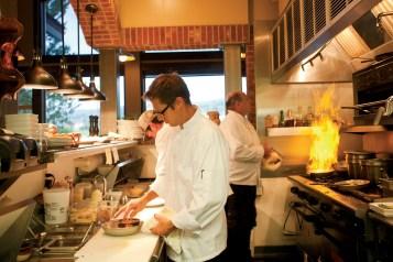 Chris Rennau, front, and Warren Bibbins, prepare entrees in the busy kitchen.