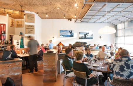 With overhead glass-paned garage doors, surf art, grass mats and warm-toned reclaimed wood, the Stillwater dining room is bright, cheerful and inviting for the business of eating.