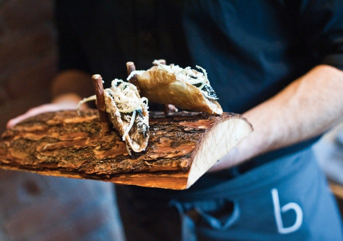The crispy chicken skin taco is topped with chicken confit, pickled kale, and pepper jack cheese.