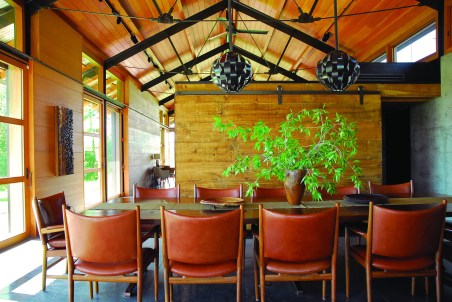 Vintage Lightolier light fixtures are suspended above a custom Claro walnut and bronze table paired with vintage Hans Wegner chairs. Sliding barn-style doors can close off the dinning room for additional privacy, but allow for an open flow to the floor plan.