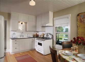 Designer Kathy Koelzer used simple painted cabinets and white tile to brighten up the kitchen; the mock-vintage appliances add to the farmhouse look.