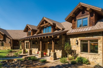 The home's front has timber framing, a shed roof of copper, Montana moss rock, and poplar bark siding.