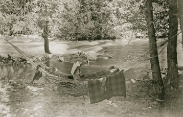 Fisherman with reader in Hammock on the Gallatin River, date unknown. Photo courtesy of Pioneer Museum, Bozeman, Mont.