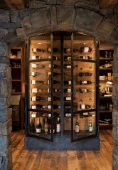 Iron-framed doors by Bar Mill Iron Forge complete the Old-World feel of this wine cellar.