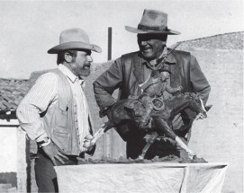 """The artist and John Wayne with the bronze of the actor's """"True Grit"""" film character, Rooster Cogburn."""
