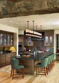 Live-edge wood and granite are used for counter and tabletops to add texture, along with the standing dead timbers that were hand-selected for their character. The base of the timbers tie into the flooring, adding a feeling of growth to the home.