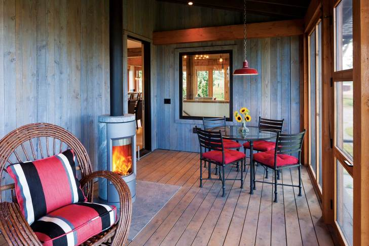 Located off of the great room, a covered porch helps keep the mosquitos at bay even while allowing fresh air to circulate. The fireplace is made from soapstone, and rotates on an axis to more evenly distribute its heat.