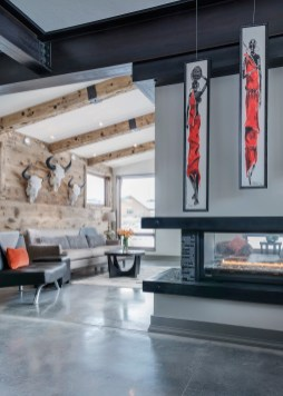Polished cement floors, recycled bridge timbers, bright red pillows, and an inviting fire accentuate the color and sweep of the Big Sky landscape.
