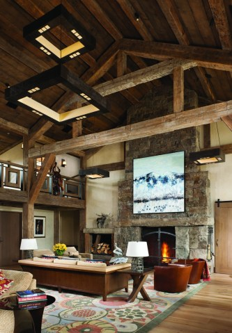 Custom light fixtures were designed by David Alexander Lighting of Oakland, California. The fireplace, made of Montana moss rock, is tall enough to stand in and is the perfect place to display an original oil by artist Theodore Waddell. The ceiling showcases the craftsmanship of its post-and-beam construction in the living room.