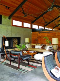 The ceiling of the home has a lightness to it yet was design to withstand heavy snow loads during the winter. The impressive, sculptural steel trusses were designed by Bill Aylor of Lake + Flato for a delicate and structural presentation. The 1970s leather and rosewood chairs by Sergio Rodrigues established the tone for the home's interiors.