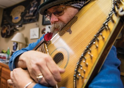 Peter Barberio plays his personal autoharp at his shop in Missoula. He has custom made 58 autoharps over the years.
