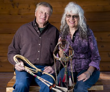 "Ron and Shoni Maulding form a great artistic duo. They have combined the art of Shoni's hitched horsehair with Ron's creative metal, rawhide, and semi-precious stonework. They are holding one of their most unique pieces, called ""Mariposa."""