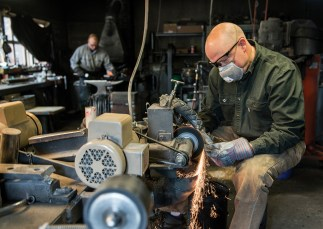 Mike Hangas, right, grinds the profile shape of a knife while his brother, Mark, prepares the forge.