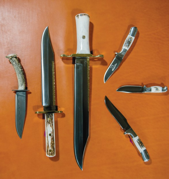 A collection of custom, collectible, and catalog knives from Ruana Knives. From left: A custom knife with a clay-hardened blade, an Early American Bowie, a Classic Bowie, a VN Hangas Special, a Smokejumper, and the Custom Finn.