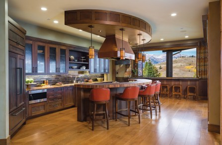 A kitchen designed for entertaining has a curved counter to emphasize the site's 180-degree views. A wall of windows above the breakfast bar folds back to create the sensation of al fresco dining.