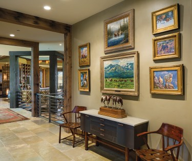 A hallway leading from the entry to the main living area showcases paintings from the owner's collection of representational Western paintings, which tie the home to its place in the world.