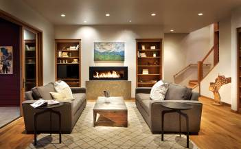 Built-in cabinets and a long, metal fireplace further impart a modern, minimalist flare in the living room.