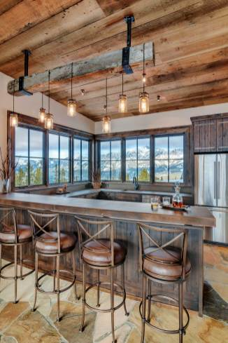 """""""We took the clients to Four Corners and picked out the reclaimed timber for the custom light fixture above the ski lounge bar, then Blue Ribbon fabricated it with Mason jar-esque lights,"""" said Bing."""