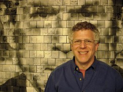"Artist Richard Notkin in front of his mural ""All Nations Have Their Moment of Foolishness."""