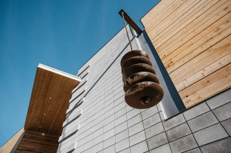 """Circles and lines; a rain chain made of five salvaged harrow disks is 102's """"water feature."""""""