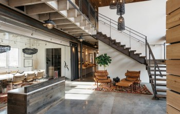 In the foyer, the cool of concrete and steel is warmed by tones from wood and leather and organic details, such as the conference room door's kudu horn handle.
